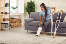 Young Smiling Woman With Broken Leg In Cast Trying To Stand Up With Crutches From Sofa At Home With Room Interior At Background. Injury, Trauma, Recovery, Rehabilitation Concept