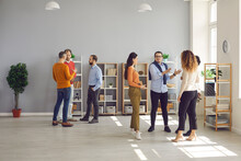 Groups Of Diverse People Standing And Talking At Company Networking Event. Men And Women Meeting In Modern Spacious Office Workspace, Exchanging Opinions And Ideas And Making Useful Business Contacts
