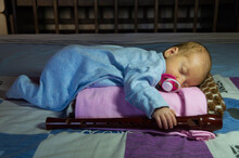 A Newborn Baby In A Blue Overalls Sleeps On His Stomach With A Block-flute In His Right Hand And A Pacifier In His Mouth