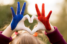 Love And Happiness Concept. Cute Child Forming Heart Gesture With Hands Outdoors On Nature Sunset Bokeh Background. Heart Shape Of Kids Hand Painted In France Flag Colors, Kids Body Language