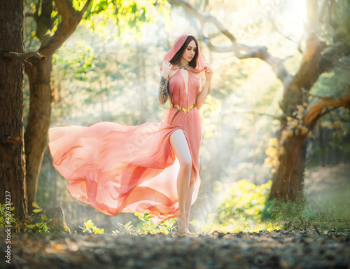 Young beautiful woman fantasy elf walks in spring forest. Green trees background, summer park. Girl princess in orange peach color silk dress, hood cape flies waving in wind motion. Sexy fashion model