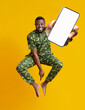 canvas print picture Barefoot happy black guy in African costume jumping up with smartphone over orange studio background, mockup