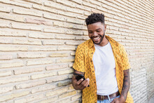 Lifestyle Portrait Of A Handsome American Man Using A Smartphone In The Street With Brick Wall As Background