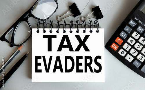 Fotografie, Obraz tax evaders. text on white paper on gray background