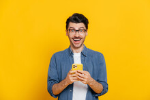 Happy Handsome Amazed Stylish Guy With Eyeglasses, Using Smartphone, Chatting Online, Writing Message, Browsing Internet, Social Media, Looks Surprised At Camera, Standing On Isolated Orange