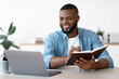 Black Millennial Freelancer Guy Taking Notes While Working On Laptop At Home