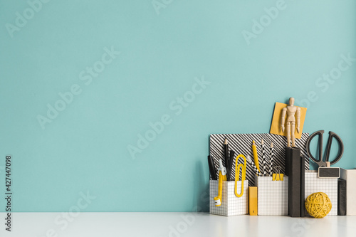 Obraz Creative desk with a blank picture frame, desk objects, drawing supplies, pencils, brushes, near bright pastel wall. Artist workspace.  - fototapety do salonu
