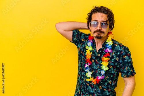 Fototapeta Young caucasian man wearing a hawaiian necklace isolated on yellow background touching back of head, thinking and making a choice. obraz