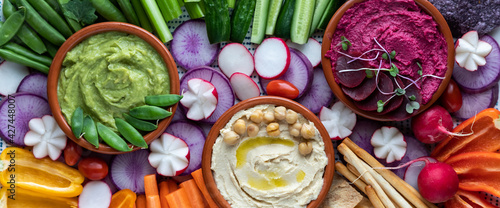 Canvastavla Narrow close up view of three dips surrounded by fresh cut vegetables for dipping
