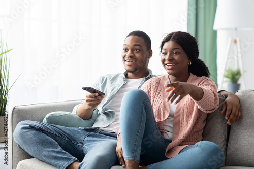 Obraz Happy african american family watching TV together at home - fototapety do salonu
