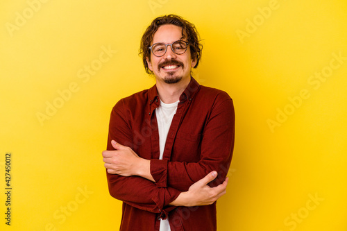 Vászonkép Young caucasian man isolated on yellow background who feels confident, crossing arms with determination