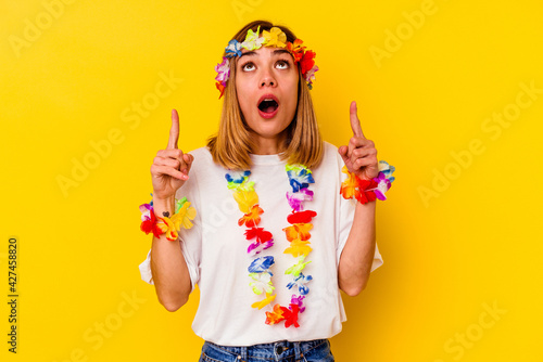 Young caucasian woman celebrating a hawaiian party isolated on yellow background pointing upside with opened mouth.