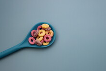 Sweet Multicolored Flakes In The Form Of A Ring In Blue Spoon On Blue Background.