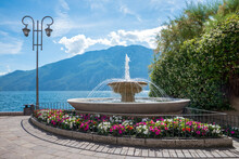 Beautiful Fountain At Lake Shore Gardasee, Tourist Resort Limone With Colorful Impatiens Flowers