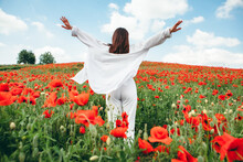 Young Pretty Woman Enjoying Life. Standing In The Middle Of The Filed With Poppy Flowers