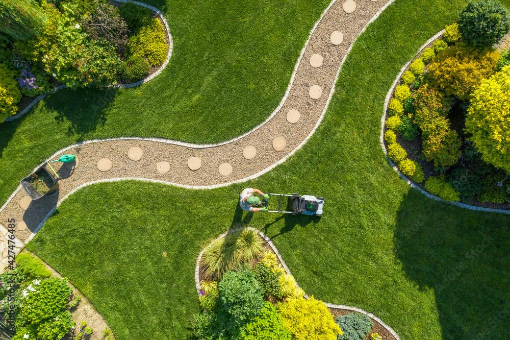 Leinwandbild Motiv - Tomasz Zajda : Big Garden Grass Field Mowing by Caucasian Gardener