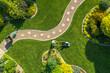 Leinwandbild Motiv Big Garden Grass Field Mowing by Caucasian Gardener