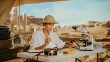Archaeological Digging Site: Great Female Archaeologist Doing Research, Uses Smartphone To Share Discovery Of Fossil Remains, Ancient Civilization Cultural Artifacts On Internet Social Media