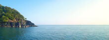Wide Horizontal Panorama Of Sea And Rocky Cliff Covered With Green Forest. Clear Sky. Line Of Horizon. Open Ocean. Expanse Of Water. Ready Template, Blank Space For Text, Logo, Inscription. Seascape