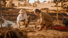 Archaeological Digging Site: Two Great Archeologists Work On Excavation Site, Carefully Cleaning With Brushes And Tools Newly Discovered Ancient Civilization Cultural Artifact, Fossil Remains