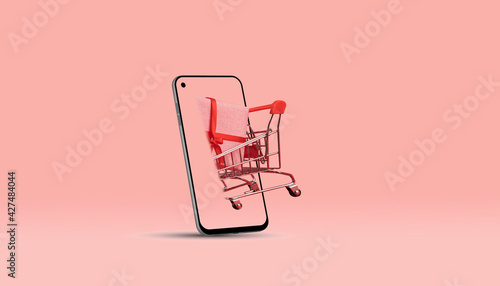 Online shopping concept. Smartphone and shopping trolley on pink background. 3d rendering. - fototapety na wymiar
