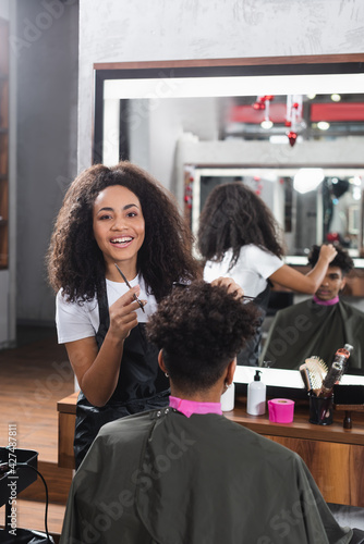 Obraz Positive african american hairdresser with comb and scissors working with client in salon - fototapety do salonu