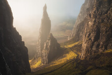 Moody, Atmospheric Fog And Mist With Golden Sunrise Or Sunset Light And Shadow At The Iconic Needle Rock Pinnacle At The Quiraing On The Trotternish Ridge, Isle Of Skye.