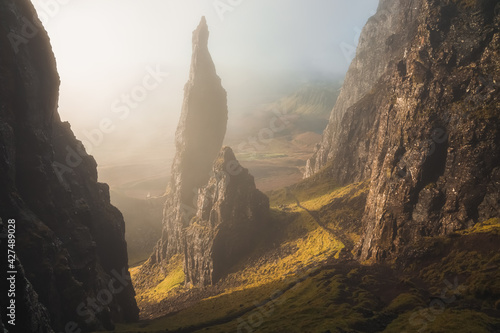 Fototapeta Moody, atmospheric fog and mist with golden sunrise or sunset light and shadow at the iconic Needle rock pinnacle at the Quiraing on the Trotternish Ridge, Isle of Skye. obraz
