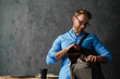 The smiling man in blue shirt and glasses looking for something in bag while standing near the table in the studio