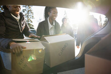 Friends Unloading Donation Boxes From Sunny Car In Parking Lot