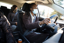Woman In Face Mask Driving Passengers In Crowdsourced Taxi