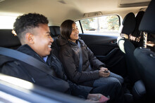 Happy Teenagers Riding In Back Seat Of Car