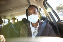 Portrait Woman In Face Mask Driving Passengers In Crowdsourced Taxi