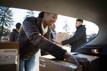 Young Woman Unloading Donation Boxes From Car In Parking Lot