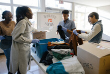 Teenage Volunteers Sorting Clothing Donations In Community Center