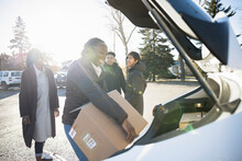 Happy Young Woman Unloading Donation Box From Car In Sunny Parking Lot