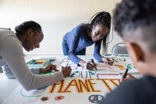 Volunteers Coloring Environmental Poster In Community Center