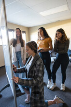 Teen Girls At Whiteboard In Book Club Meeting In Community Center