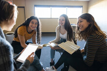 Happy Teen Girls Reading In Circle At Book Club Meeting