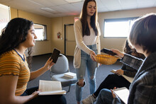 Teen Girls Putting Smart Phones Into Basket At Book Club Meeting