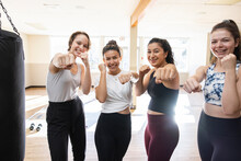 Portrait Confident Smiling Teen Girls In Boxing Fighting Stance In Gym