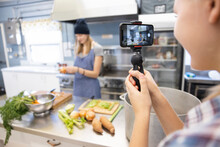 Teen Girl With Smart Phone Filming Cooking Class In Kitchen