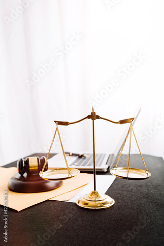 Photo Close up of hand lawyer working signing contract paper with wooden gavel judge in the office