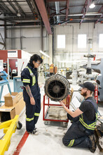 Man And Woman Working On Helicopter Component