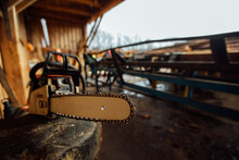 The Chainsaw Is Lying On The Sawmill. A Tool For The Work Of A Woodcutter. Wood Harvesting At The Factory
