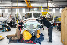 Mechanic Passing Tool To Colleague Working On Helicopter
