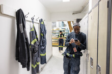 Worker Standing Next To Locker With Phone