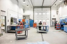 Technicians Working In Helicopter Hangar