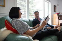 Senior Couple Relaxing With Magazine On Sofa