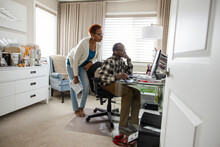 Senior Couple Using Computer In Home Office